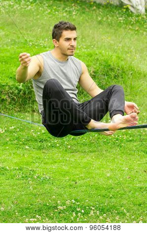 Man sitting on slackline concentrating to keep balance with grassy background