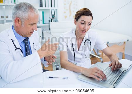 Concentrated medical colleagues discussing and working with laptop in the hospital