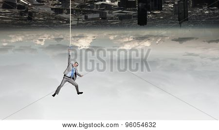 Young businessman hanging on rope above city