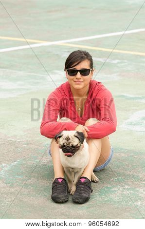 Hispanic beautiful woman with sunglasses and pug dog sitting together in a tennis court