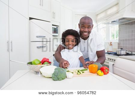 Little boy cooking with his father in the kitchen