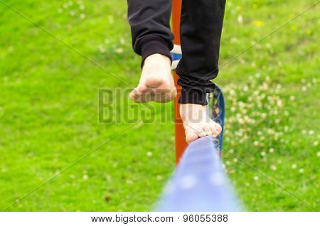 Closeup of mans feet balancing a tightrope or slackline in park environment with one foot above rope