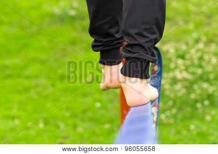 Closeup mans feet from behind balancing on slackline with grassy background