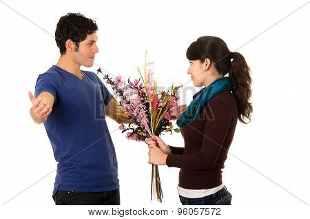 Hispanic couple facing each other and woman holding flowers while man looks upset