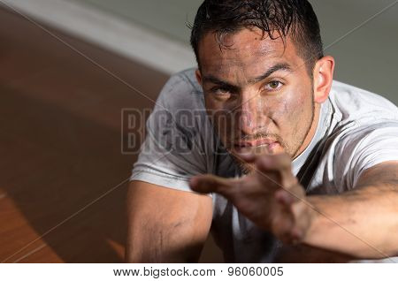 Hispanic man with dirty face and shirt lying on floor looking desperately to camera reaching left ha