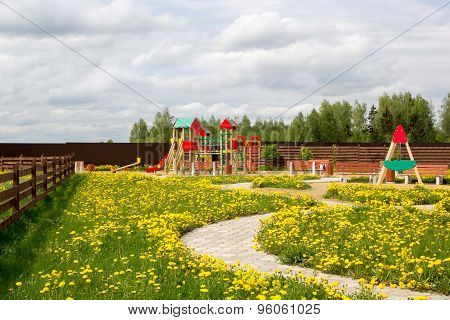 Children Playground Among Blossoming Dandelions