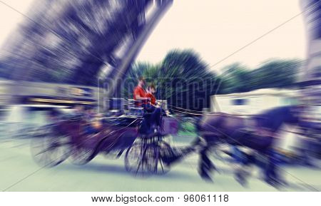 Abstract Background. Paris, Tourists In Carriage With Horses Near The Eiffel Tower. Defocusing Filte