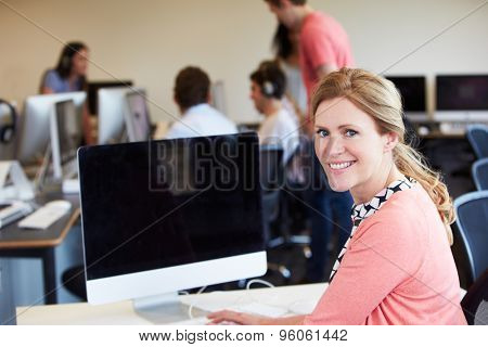 Female Tutor Using Computer In IT Class