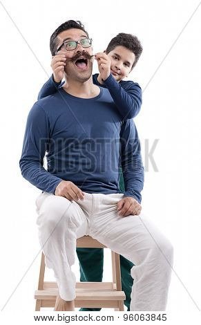 Cute boy pulling his father's mustache isolated on white background.