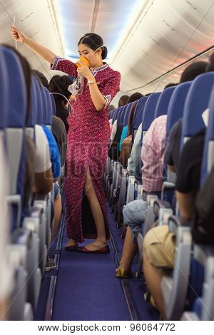 BANGKOK, THAILAND, DECEMBER 29, 2014 : A air hostess of the Thai Lion Air company is showing how to use oxygen mask before taking off from the Suvarnabhum airport in Bangkok, Thailand
