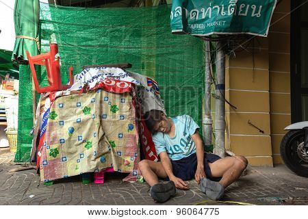 BANGKOK, THAILAND, FEBRUARY 18 , 2014 : Drunk man lying in a small street of the Phra Nakhon district during the Chinese new year celebration in Bangkok, Thailand