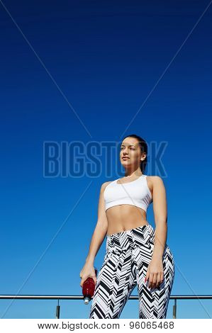 Healthy woman with beautiful figure enjoying sunny afternoon during her daily workout training
