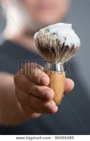 Man Is Holding A Shaving Brush In The Hand