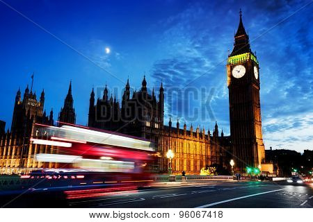 Red bus in motion, Big Ben and Westminster Palace in London, the UK. at night. View from Westminster Bridge. Moon shining on dark blue sky