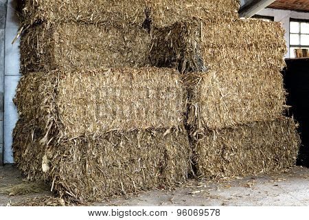 Stacked Rectangular Hay Bales In A Barn