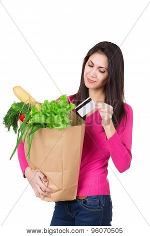 Beautiful young woman with credit card holding groceries in eco paper bag. Female consumer at grocer