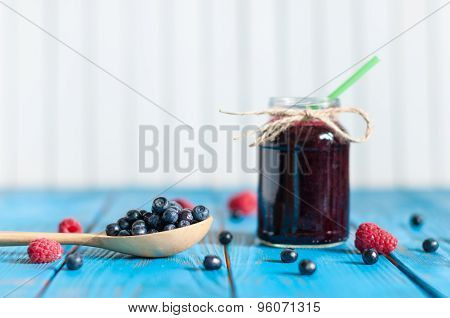 Blueberry smoothie or homemade jam in mason jar with fresh berries on light rural background. Select