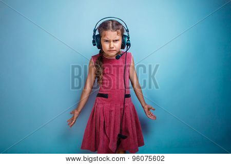 Teen girl child dissatisfied evil in headphones with a microphon