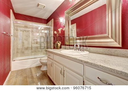 Classy Bathroom With Red Walls, And White Cabinets.
