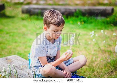 Boy sitting on a bench with soap bubbles