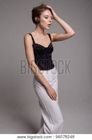 woman in black blouse and white trousers
