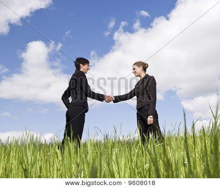 Women shaking hands outdoors