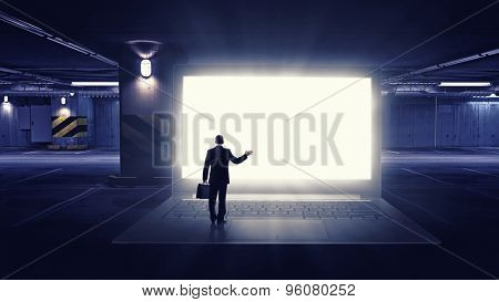 Rear view of businessman with suitcase standing on keyboard of big laptop