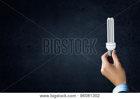 Close up of businessman hand holding glass light bulb