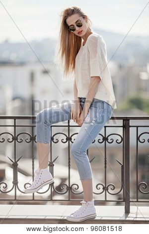 Fashion model. Summer look. Jeans, sweater, sunglasses.