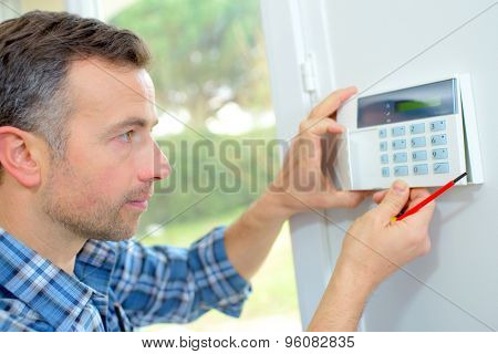 Electrician fitting an intrusion alarm