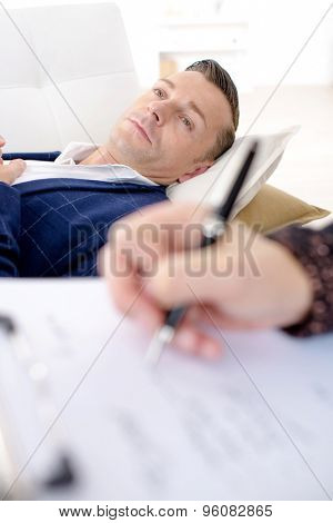 Man laying on couch, woman taking notes