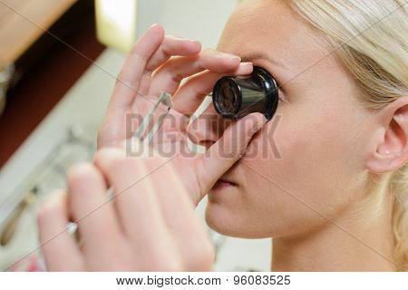 Female jeweller assessing a stone