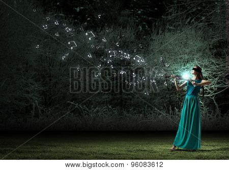 Attractive woman in long green dress playing violin