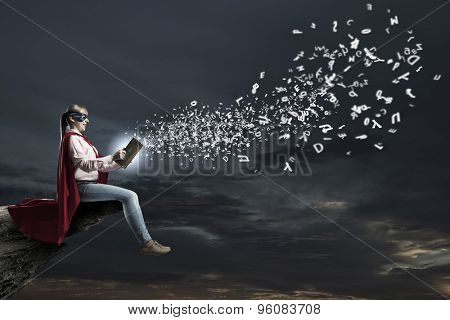 Young woman in super hero costume reading book