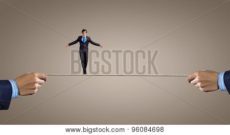 Young brave ricky businessman balancing on rope