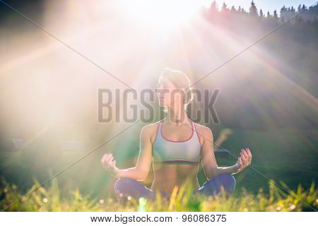 Woman doing yoga in sunset, backlit situation