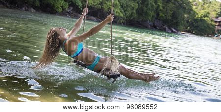 Woman In Blue Bikini On Rope Swings