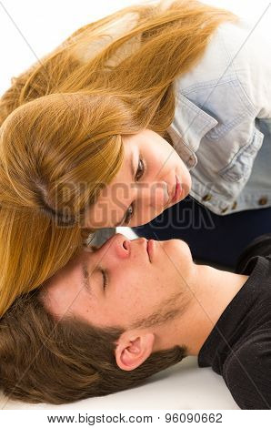Couple demonstrating first aid techniques with female helper placing her ear over patients mouth lis