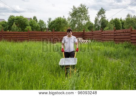 Man With Empty Wheelbarrow In The Grass