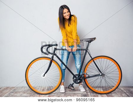 Full length portrait of a smiling woman standing near bicycle on gray background. Looking at camera