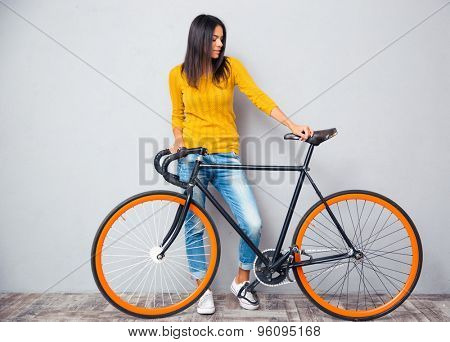 Casual young woman standing with bicycle on gray background