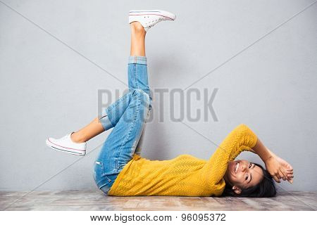 Happy casual woman lying on the floor with raised legs up over gray background and looking at camera