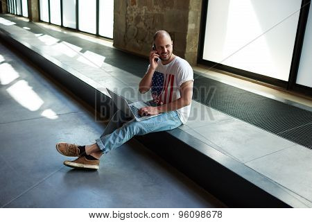 Young man starting business sitting on the floor with laptop computer while discussing design