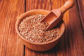 stock photo of flax seed oil  - The flax seeds in a wooden bowl close up - JPG