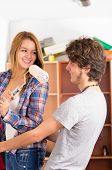 picture of she-male  - Couple renovating together as she holds up a roller with pink paint in front of his face smiling to each other - JPG
