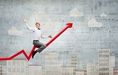 stock photo of tame  - Concept of anti crisis with businessman that tames statistics diagram - JPG