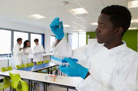 stock photo of experiments  - Group Of College Students In Science Class With Experiment - JPG