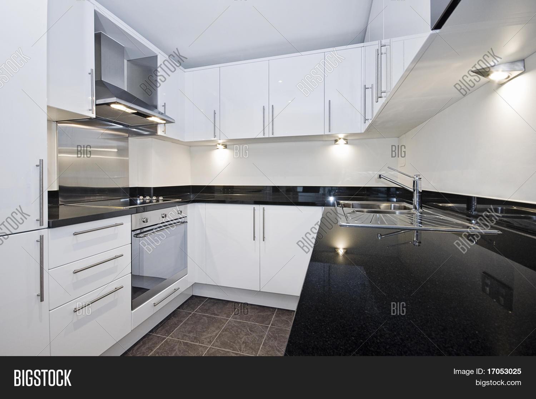 Hedendaagse luxe keuken in wit met zwarte stenen aanrecht stock ...