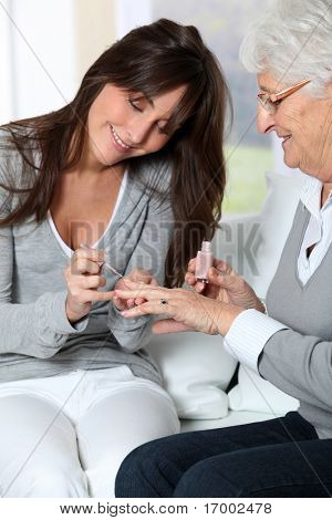 Young woman putting nail polish to elderly woman