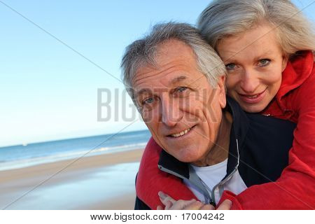 Senior man giving piggyback ride to woman by the sea